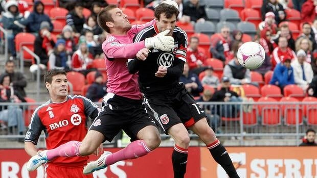 Milos Kocic (30) of Toronto FC makes the save around Chris Pontius (13) of D.C. United during MLS action at BMO Field on Saturday.