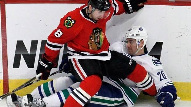Blackhawks' Nick Leddy checks Canucks' Chris Higgins along the boards in a game last season.