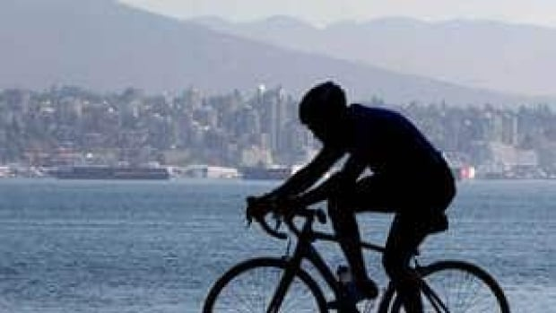A cyclist is silhouetted against the North Shore mountains while riding through Vancouver's Stanley Park.
