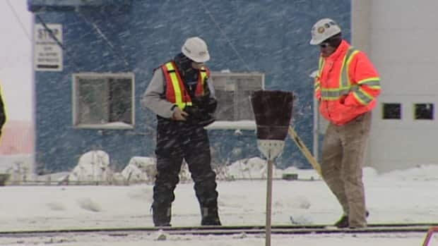 Rail workers investigate a section of track after three contractors were hit while clearing snow east of Edmonton.