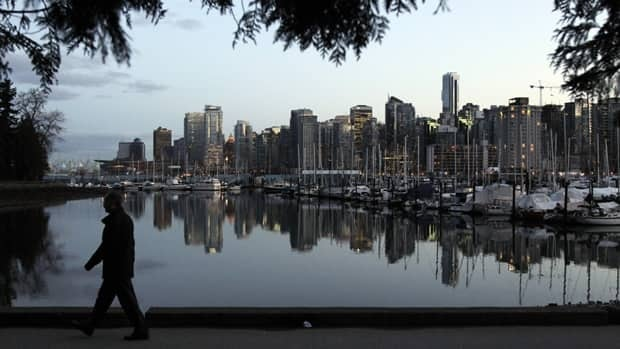 A man walks in Stanley Park as the skyline of Vancouver is reflected in the water in Vancouver in February 2010.