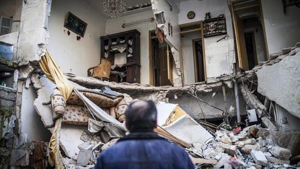 A civilian looks Thursday at a destroyed home in Aleppo, Syria, which is immersed in a Syrian civil war that the United Nations estimates has killed more than 60,000 people since March 2011.