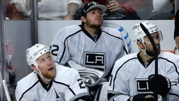 Los Angeles Kings goalie Jonathan Quick, centre, sits on the bench between defenceman Matt Greene, left, and Alec Martinez during the third period in Game 2 against the Chicago Blackhawks Sunday.