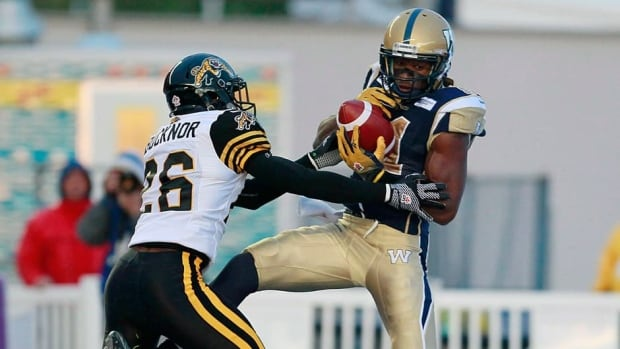 Winnipeg Blue Bombers' Cory Watson, right, catches a pass in the end zone against the Tiger-Cats on September 21, 2012.