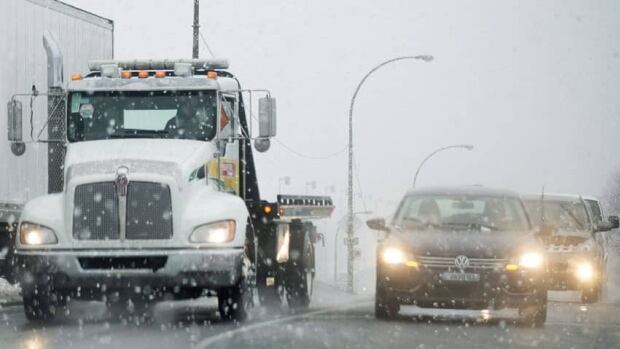 Cars make their way along a road as snow falls in Montreal on Friday. The messy weather in parts of the country continued Saturday.