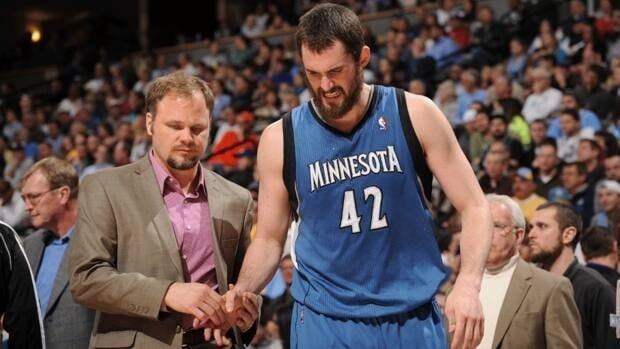 Kevin Love of the Minnesota Timberwolves has the trainer look at his hand after he jammed his finger against the Denver Nuggets on Thursday.