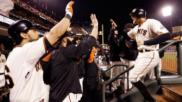 San Francisco Giants outfielder Hunter Pence is congratulated in the dugout after scoring during the seventh inning of Game 2 of the World Series against the Detroit Tigers on Thursday.