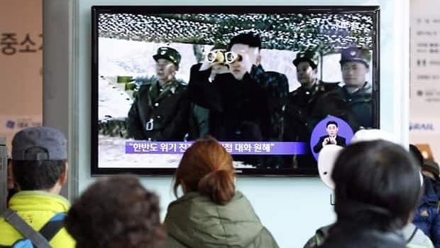 South Koreans watch a TV program showing North Korean leader Kim Jong-un at Seoul Railway Station on April 7.