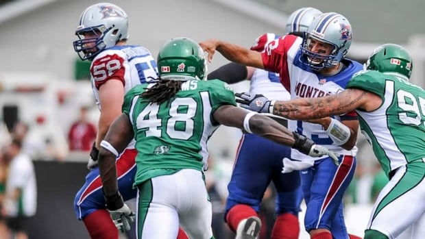 Montreal Alouettes quarterback Anthony Calvillo, second from right, throws the ball under pressure from Saskatchewan Roughriders linebacker Renauld Williams, second from left, and defensive end Ricky Foley, right on Saturday. Calvillo would leave and not return after taking a hit from Foley.