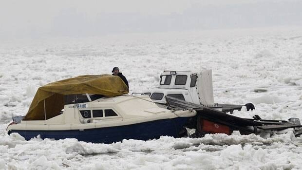 A man looks at damaged boats on a frozen part of the Danube River, in Belgrade, Serbia, on Monday. Big chunks of melting ice moving on the Danube River have damaged hundreds of small boats and several restaurants located on rafts, officials said Monday.