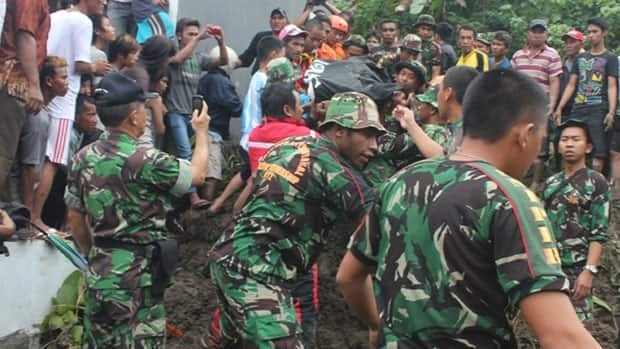Rescuers search for the victims of a landslide in Manado, North Sulawesi, Indonesia, Sunday, Feb. 17, 2013.