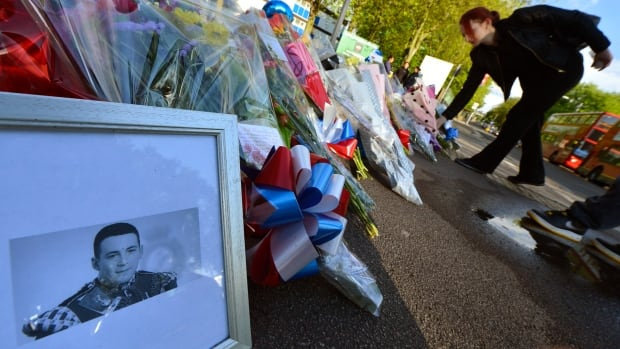 A picture of victim Drummer Lee Rigby, of the British Army's 2nd Battalion The Royal Regiment of Fusiliers is displayed with flowers left by mourners outside an army barracks near the scene of his killing in Woolwich, southeast London on May 23, 2013. British authorities believe that two men accused of hacking a soldier to death on a London street in revenge for wars in Muslim countries are British of Nigerian descent, a source close to the investigation said Thursday.