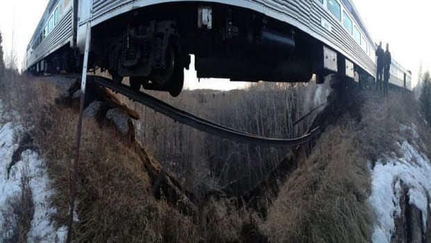 This Via Rail train derailed after going over a washed-out section of track near Togo, Sask., on Sunday. The panoramic photo has also been squeezed to fit this page.