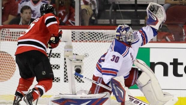 New York Rangers goalie Henrik Lundqvist, right, stops a shot as New Jersey Devils right wing Dainius Zubrus, looks for a rebound during the first period of Game 3 in Newark, N.J.