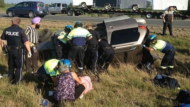 Emergency crews and witnesses surround a damaged minivan following a fatal crash Monday on Highway 401 near Tilbury.