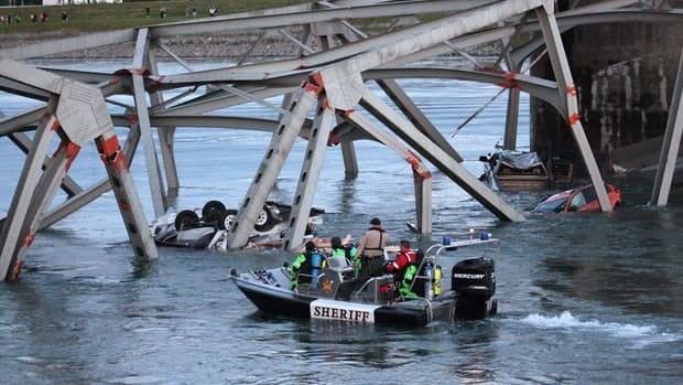 A rescue boat approaches the scene where a pickup truck and travel trailer, seen at left, and a car fell into the Skagit River.