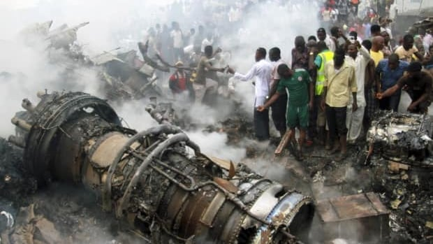 People gather near the engine of a plane after it crashed into a neighbourhood in Ishaga district, an outskirt of Nigeria's commercial capital Lagos on June 3.