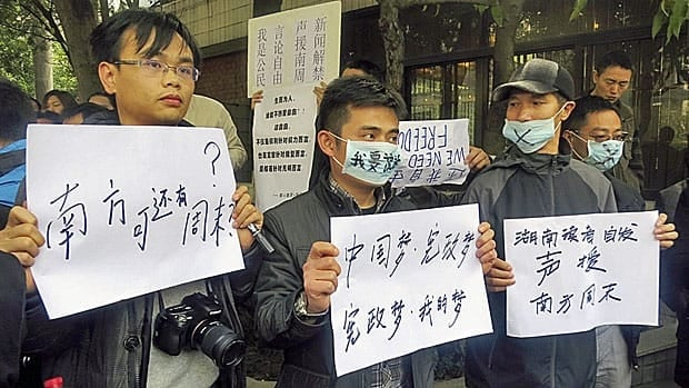 Journalists and other anti-censorship protestors hold banners outside the headquarters of Southern Weekly newspaper in Guangzhou, Guangdong province, in early January. The Chinese characters on the mask read I want to speak