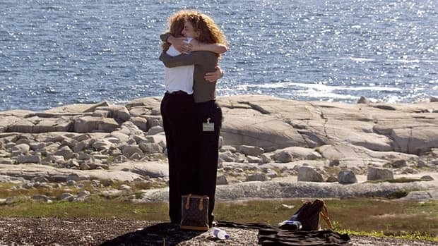 Relatives of those killed embrace on the shore of Peggy's Cove in 1999 during ceremonies marking the first anniversary of the crash.