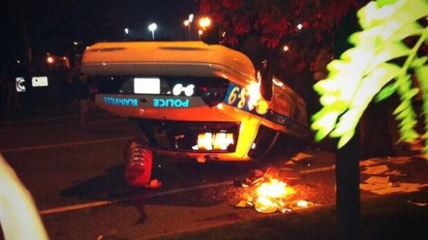 A rowdy group of people chucked bricks at police and tipped over a police car after a festival in Blainville.