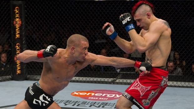 England's Dan (The Outlaw) Hardy, right, tries to evade a punch from UFC welterweight champion Georges St-Pierre during a 2010 bout.