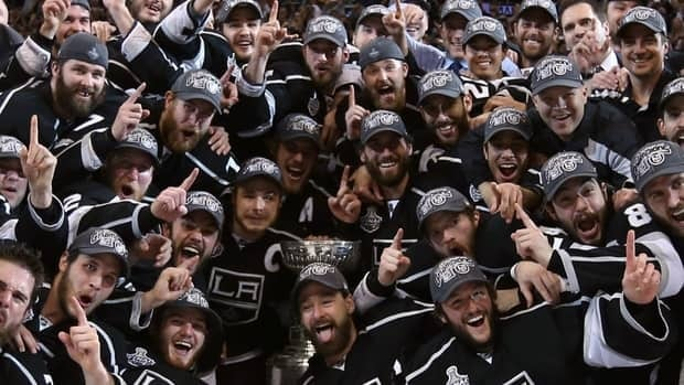 Captain Dustin Brown (23), assistant captain Anze Kopitar (11) and other members of the Los Angeles Kings surround the Stanley Cup during a group photo after the Kings defeated the New Jersey Devils 6-1 on Monday.