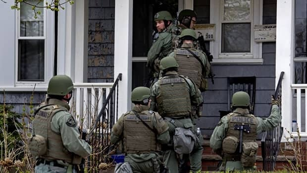 Heavily armed police officers do house to house searches the neighborhoods of Watertown, Mass.  as a massive search continued for one of two suspects in the Boston Marathon bombing.