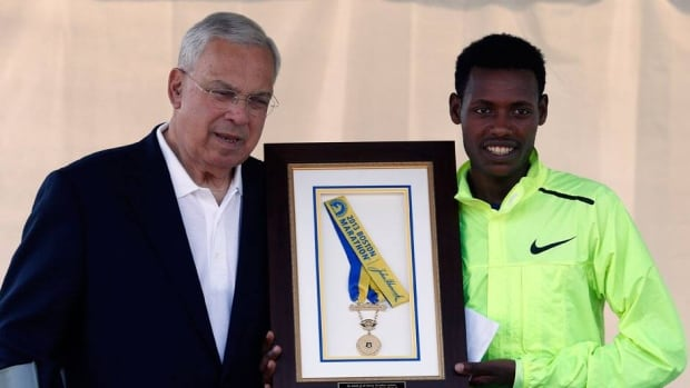Boston Marathon 2013 men's winner Lelisa Desisa, right, of Ethiopia, holds his medal with Boston Mayor Thomas Menino after presenting it to the city as a tribute to the victims of the Boston Marathon bombings.