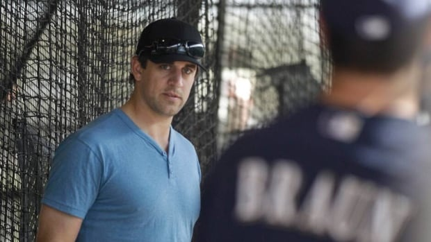 In this file photo from Feb. 29, 2012, Milwaukee Brewers' Ryan Braun, right, and Green Bay Packers quarterback Aaron Rodgers chat during a spring training baseball workout in Phoenix.