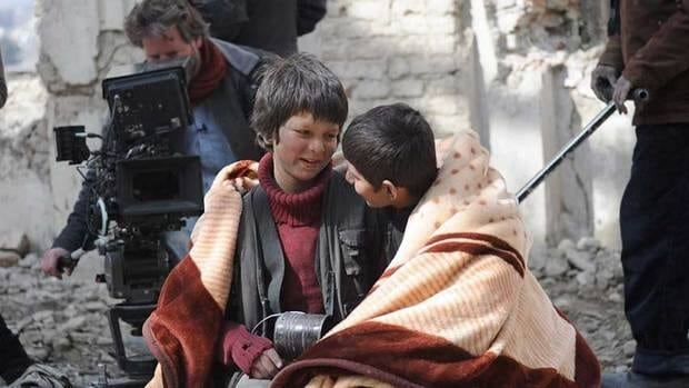 Jawanmard Paiz, centre, and Fawad Mohammadi, right, star as boys of different backgrounds who become friends in Buzkashi Boys.  Director Sam French, left, is show at work on the set in Kabul.