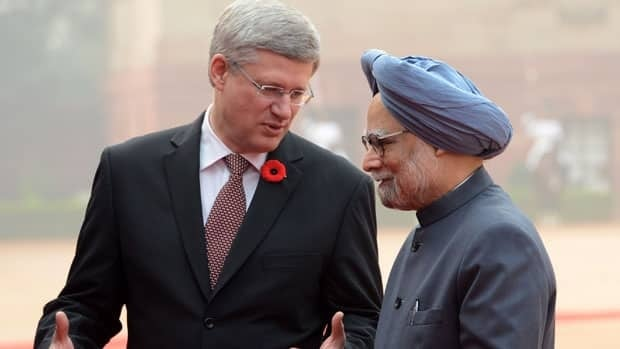 Prime Minister Stephen Harper is greeted Tuesday by Indian Prime Minister Manmohan Singh as he arrives at the presidential palace for the official welcoming ceremony in New Dehli.
