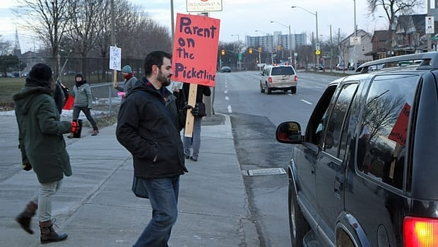Protesters picket in front of entrances to the parking lot at Sir. John A. Macdonald Secondary School on Wednesday. The group of about 30 community members was demonstrating in support of Ontario's public secondary school teachers.