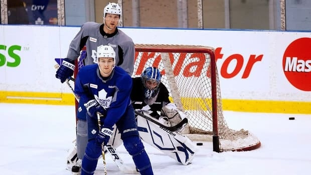 Toronto Maple Leafs forward James van Riemsdyk, left, forward David Steckel, centre, and goalie James Reimer watch the puck down the ice during the team's first day of training camp Tuesday in Toronto.
