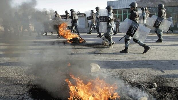 Afghan policemen walk past burning tires during an anti-U.S. demonstration in Kabul. Thousands of Afghans staged new demonstrations Saturday over the burning of Qur'ans at a U.S. military base in Afghanistan.