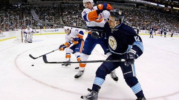 Pittsburgh Penguins' Jarome Iginla (12) is checked by New York Islanders defenseman Travis Hamonic (3) as he gets off a pass in an NHL hockey game in Pittsburgh on March 30, 2013.