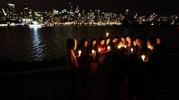 A group of friends in Vancouver's Stanley Park hold candles as they gather for Earth Hour 2010.