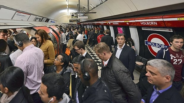 Commuters board a train at London's Holborn tube station. The British recession deepened last quarter, new data showed Wednesday.