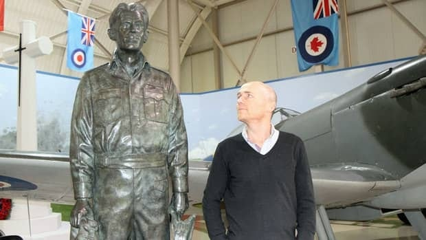 Nick Godwin, who helped produce Air Aces with Toronto-based Cineflix Productions, examines the statue of George 'Buzz' Beurling at the Canadian Warplane Heritage Museum in Hamilton. In the background is a Spitfire used in the documentary series.