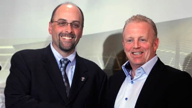 Jeff Hunt, president of Ottawa Sports and Entertainment Group, right, shakes hands with Marcel Desjardins as he is named the general manager of Ottawa's new CFL franchise in Ottawa on Wednesday.