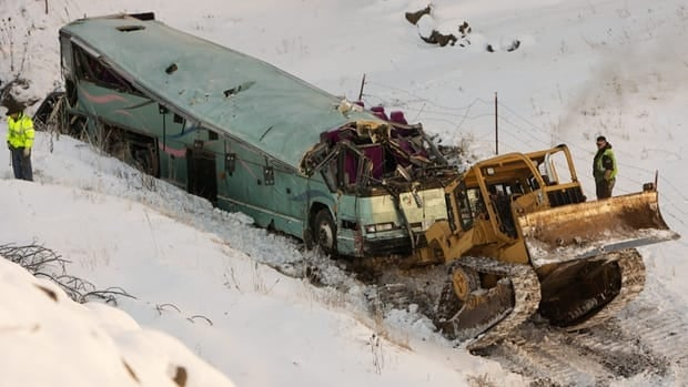 A piece of heavy equipment strains to move a bus that plummeted about 65 metres down an embankment in eastern Oregon on Sunday, killing nine.