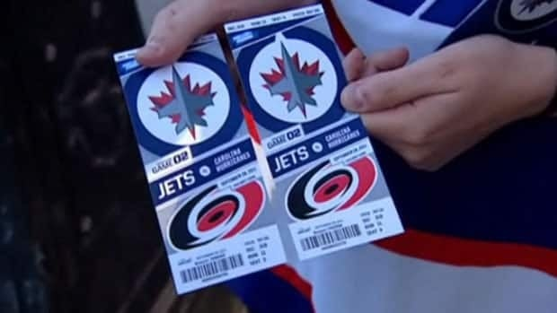 A Winnipeg Jets fan holds up tickets to a home game against the Carolina Hurricanes early in the 2011-12 season. Jets tickets were generally hard to get during the team's inaugural year in the city, with games sold out throughout the season.