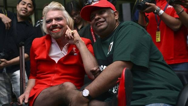British billionaire Richard Branson, left, poses with AirAsia's Chief Executive Tony Fernandes while dressed up as an AirAsia flight attendant Sunday, May 12, 2013.