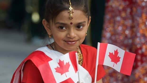 Shahnaz Begum waves two Canadian flags during Canada Day celebrations in Montreal in 2011.