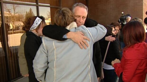 Families of the crash victims embrace outside the courthouse in Leduc, Alta. on Thursday.