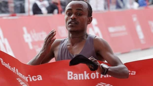 Tsegaye Kebede, of Ethiopia, crosses the finish line to win the Chicago Marathon in record tim on Sunday.