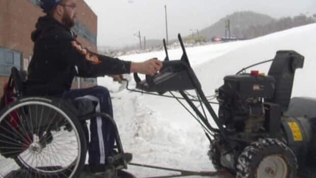 Michael Johnson demonstrates his wheelchair accessible snowblower. CBC