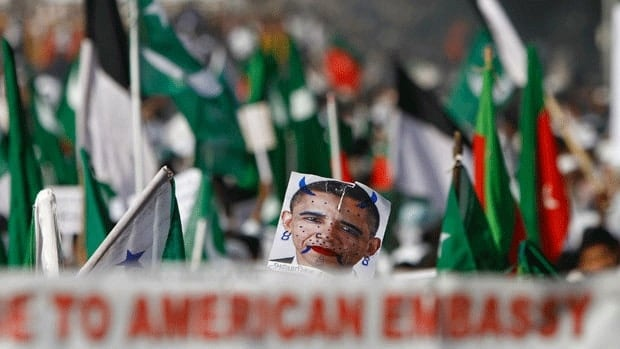 Thousands of Muslim protesters, outraged by a video made in America they consider blasphemous to Islam, carry flags and defaced pictures of U.S. President Barack Obama.