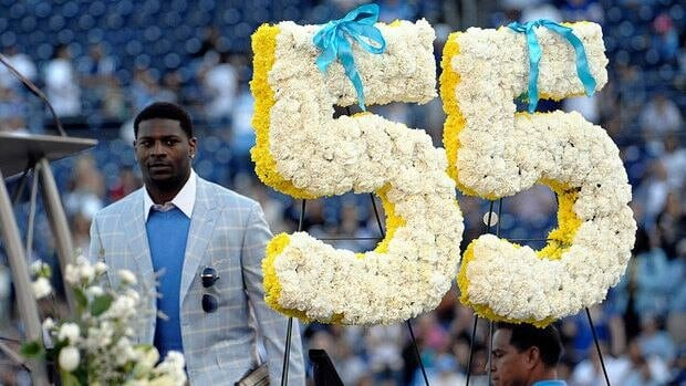 RB LaDainian Tomlinson walks past Junior Seau's #55 during a public memorial for the former NFL star.