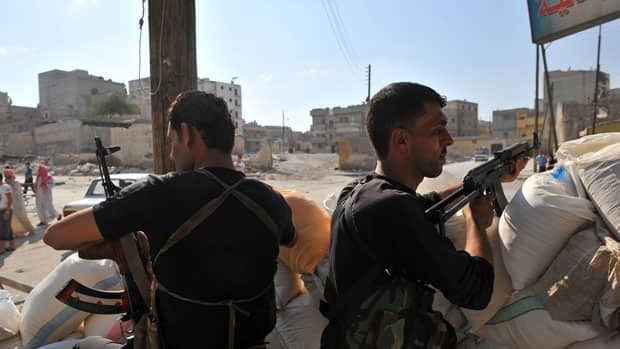 Syrian rebels man a checkpoint in the northern city of Aleppo on Tuesday. The commercial hub has become a new front in the country's 16-month uprising after being largely excluded from the violence.