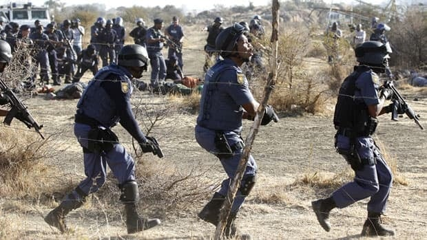 Policemen react after firing shots at protesting miners outside a South African mine on Thursday in Rustenburg, 70 kilometres northwest of Johannesburg.